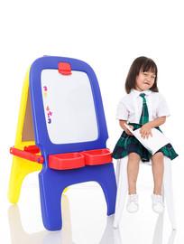 小女孩坐凳子上拿着书搞怪表情