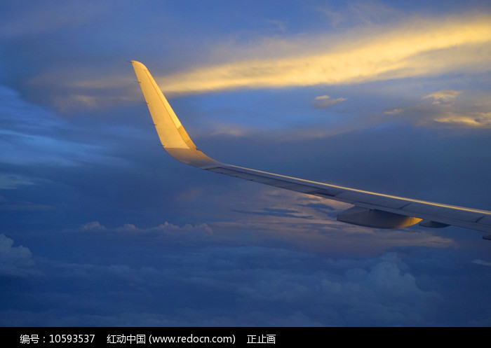 傍晚金色晚霞中行的飞机机翼图片
