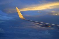 傍晚金色晚霞中行的飞机机翼