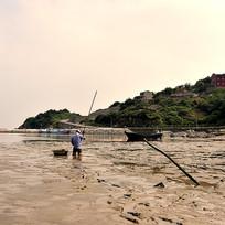 正在捕捉螃蟹的赶海人