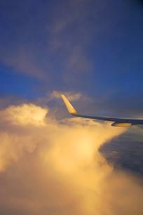 航拍金色云层中的民航客机机翼