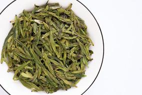 盛在白盘子里的西湖龙井茶叶