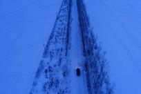 航拍雪原道路上一辆越野车行驶
