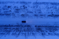航拍雪原夜路越野车