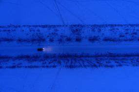 一辆越野车在雪夜道路上行驶