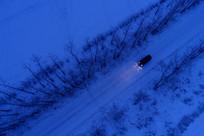 越野车在雪原夜路上行驶