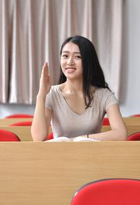 举手回答问题的美女大学生