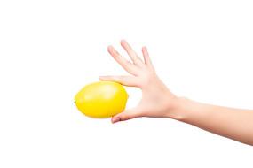 一只手拿着一个黄色的柠檬