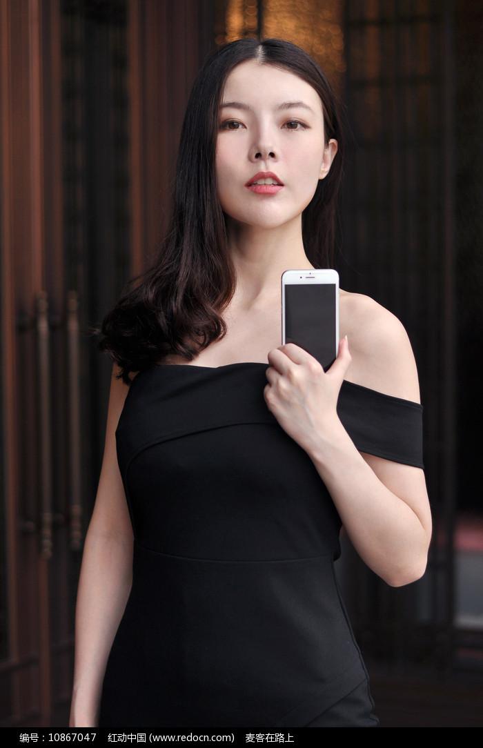 展示手机的美女模特图片