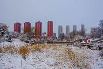 孤岛凉亭折形石桥与住宅群雪景