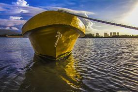 仰拍朝阳映衬下的船与大海