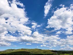 蓝天白云下的草原山丘