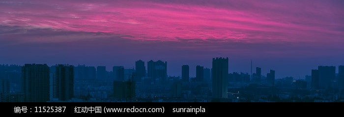 宽幅朝阳映衬下的城市轮廓图片